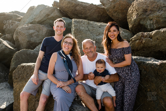Family of Five Smiling for Camera Sitting on Rocks at Beach