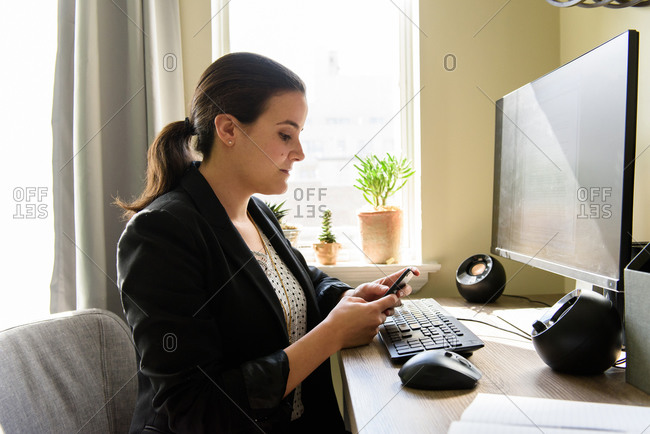 Mid adult woman working from home and texting co-workers at computer