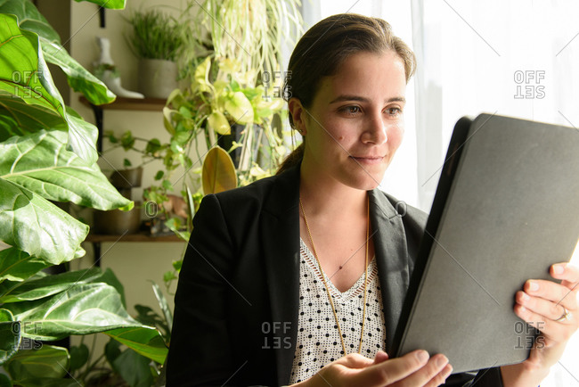 Mid adult woman reading tablet in plant filled home