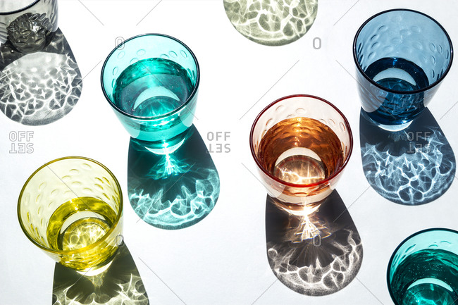 Set of color glass cups under a strong light that projects its shadows