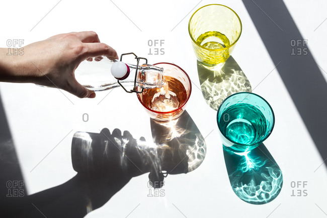 A person pours water into colored glass cups under the strong sunlight