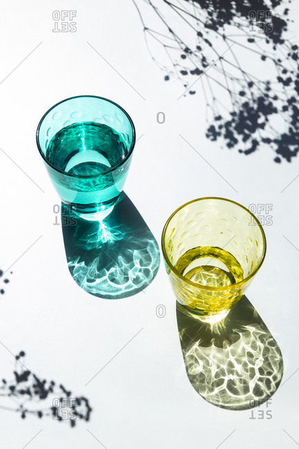 Two colored glass cups filled with water next to flowers in sunlight