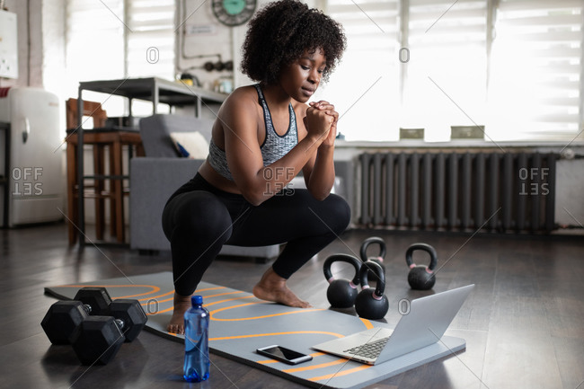 African American sportswoman squatting during online workout