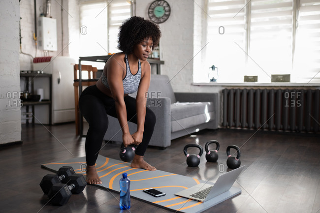 Ethnic sportswoman lifting kettlebell during online training