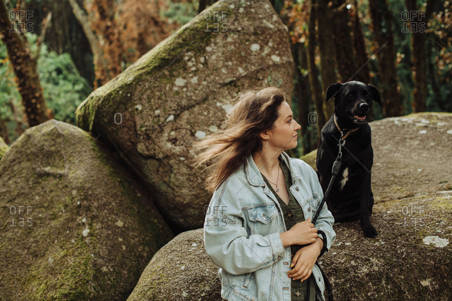 Girl looking at a black dog on a leash sitting on rock in the forest