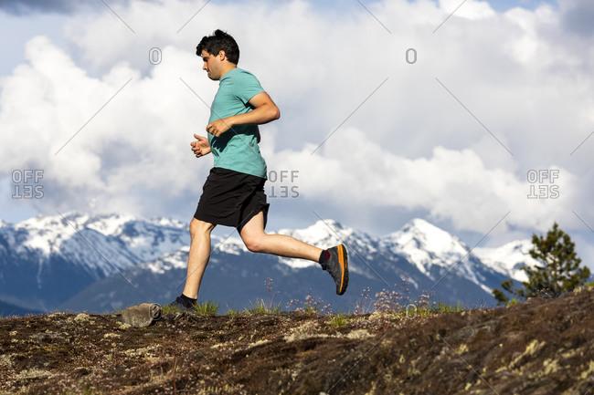 Man trail runs on a scenic alpine mountain trail in British Columbia.