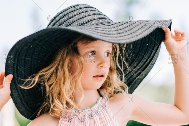 candid close up portrait of a young girl stood outside with a sun hat
