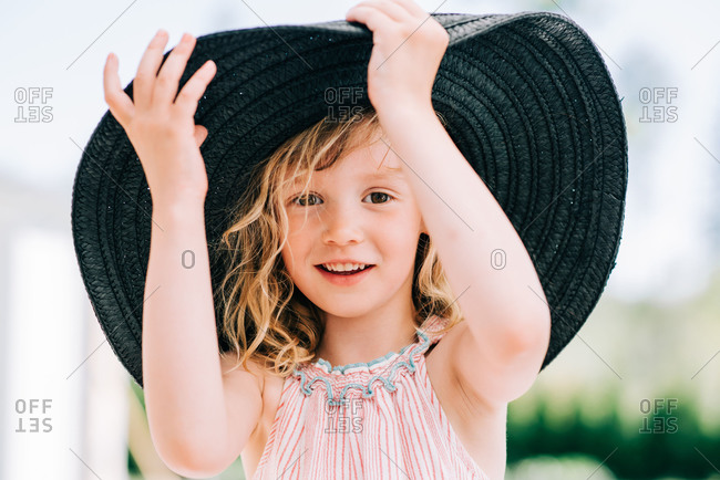candid portrait of a young girl laughing playing with a large sun hat