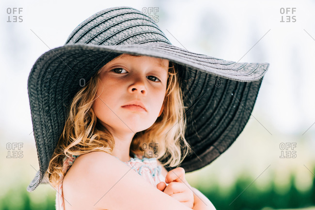 portrait of a sassy young girl staring at the camera with a sun hat on