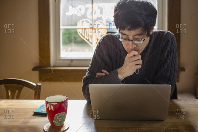 A man sits at a dining room table on computer working from home