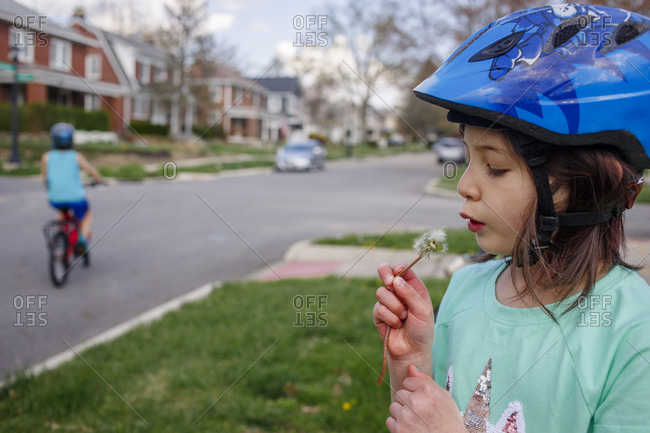 A little girl blows on dandelion while boy bikes on street behind her