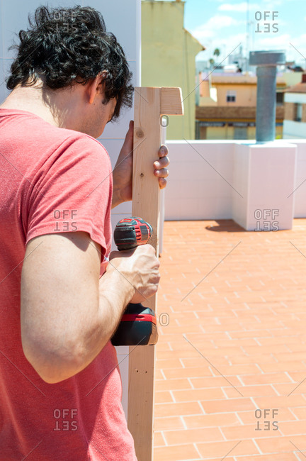 Man using a drill to build a shelf on a rooftop during a sunny day.