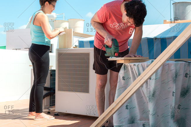 Couple working together to build furniture on the rooftop of a house.