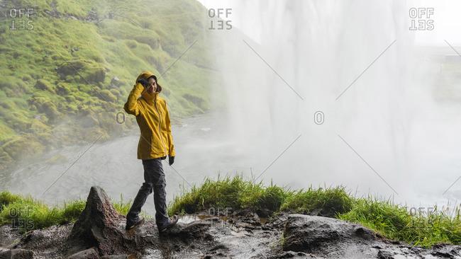 Happy female hiker in a bright rain coat behind powerful waterfall
