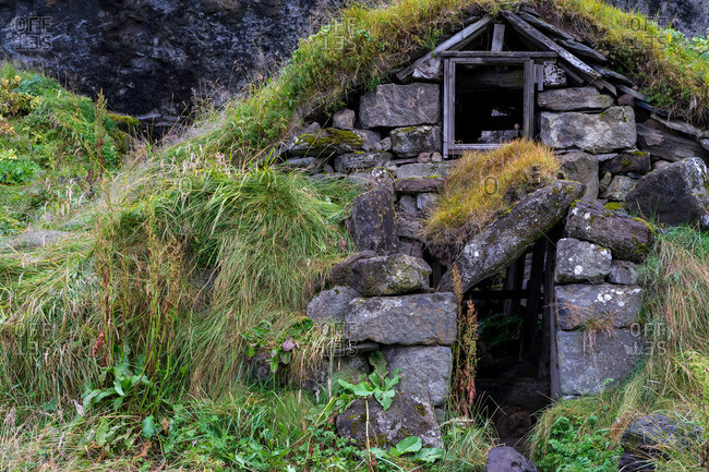 Old hut ruins built form rocks in Iceland with grass covered roof