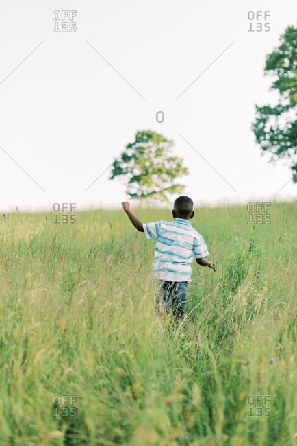 Sweet little boy running through a meadow at sunset