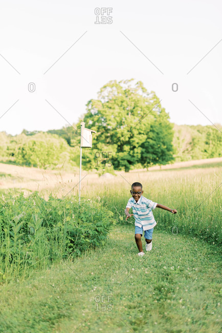 A four year old running along a path in a field