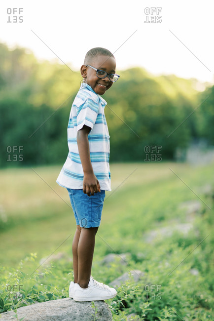 A sweet little boy standing on a rock wall