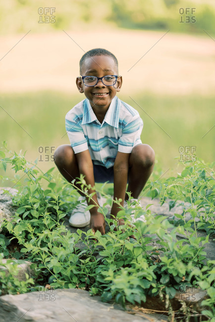 Sweet little boy playing on a Rockwell that is covered in vines