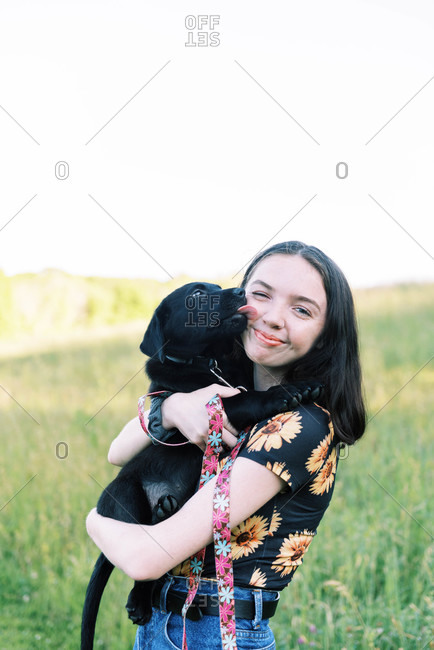 A teenage girl holding her two month old black Labrador puppy