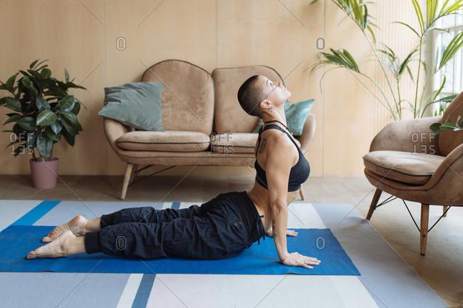 athletic skin head woman in snake yoga bhujangasana pose at home