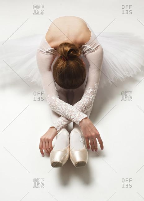 attractive ballerina in white ballet dress sitting on floor bent over