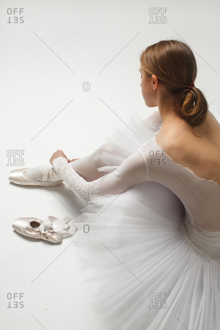 ballet dancer tying her ballet shoes around her ankle on white floor