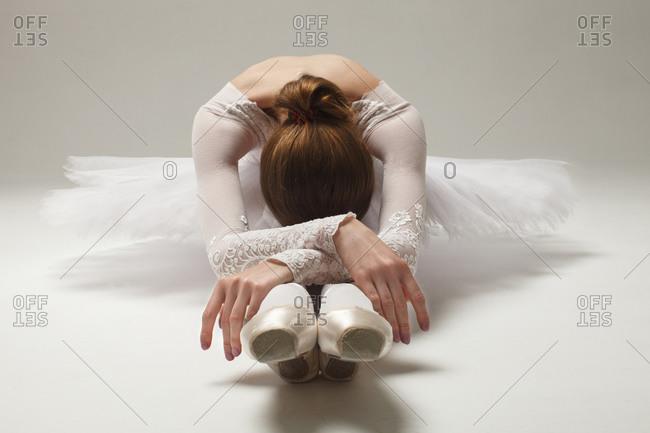 Beautiful ballerina in white ballet dress sitting on floor bent over