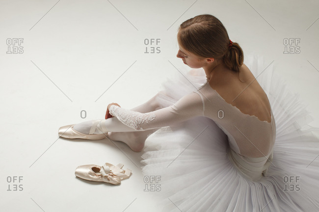 young ballerina in white ballet dress Putting On Ballet Shoes, sitting