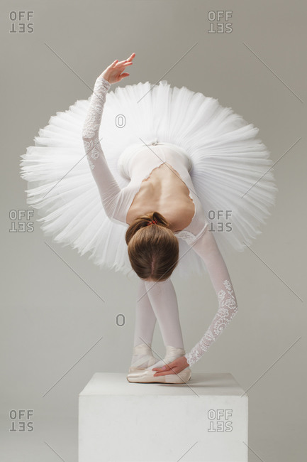 ballet dancer in white ballet tutu bowing on pedestal, isolated gray