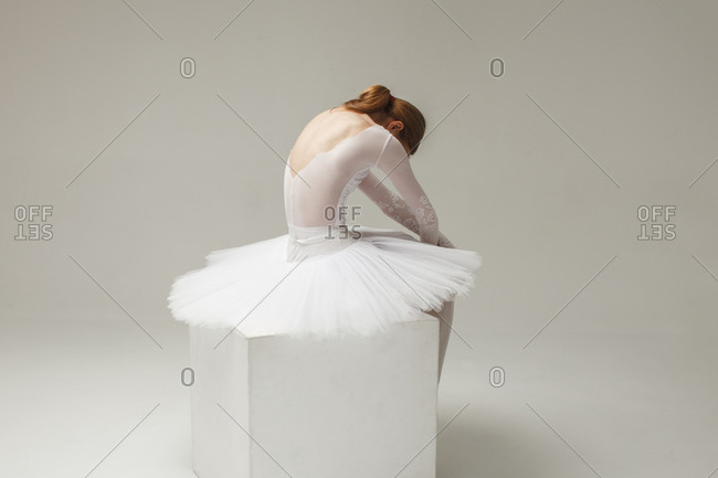 Ballerina in white ballet dress sitting on cube isolated on background