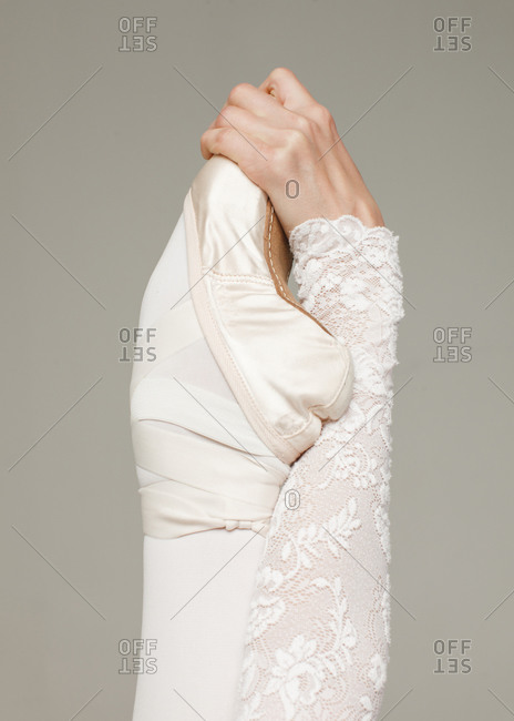 female hand holds feet in ballet shoe toe isolated on gray background