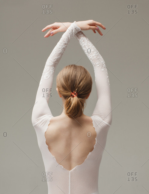 Young beautiful woman in ballet pose isolated on gray background, rear