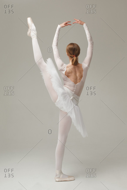 professional ballet dancer doing ballet move developpe, studio shot