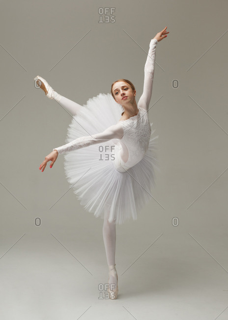 beautiful female ballet dancer in white ballet dress dancing tiptoe