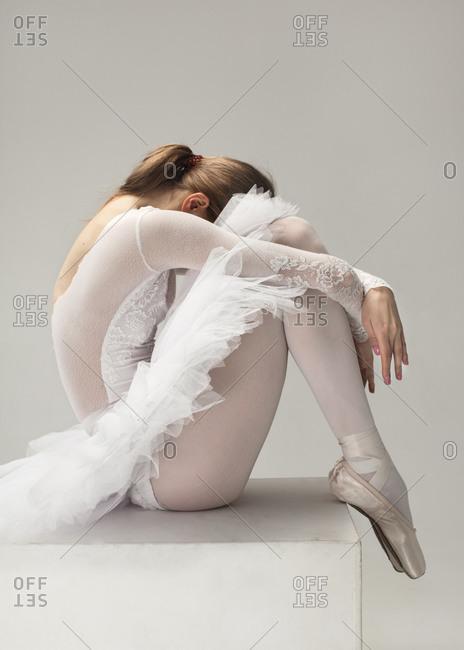 tired ballerina in white ballet dress sit on cube in fetal position