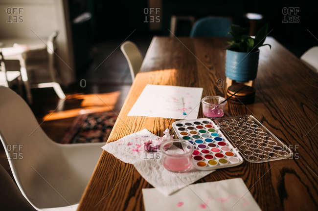 Palette of watercolor sitting on dining room table in window light