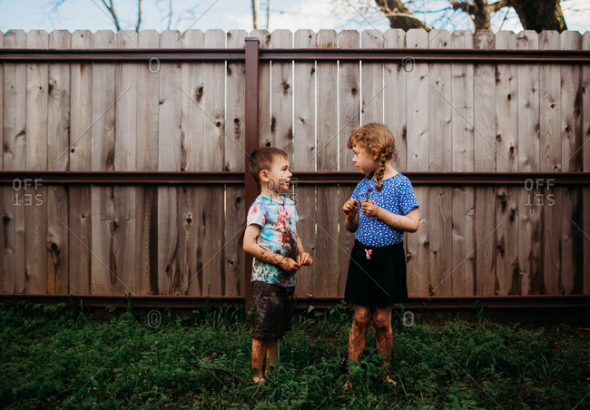 Two young kids standing outside talking covered in mud