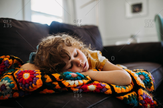 Young girl tired and sleeping on couch during the day