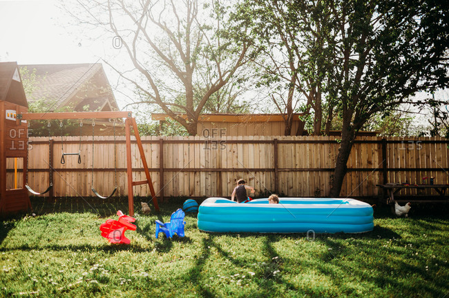 Two young kids swimming in backyard pool by swing set