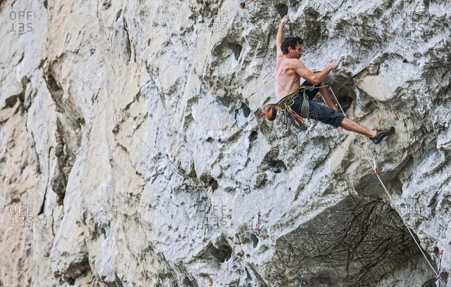 young man climbing overhang in Yangshuo / China