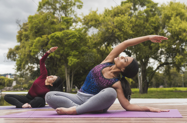 Two women making yoga on the park