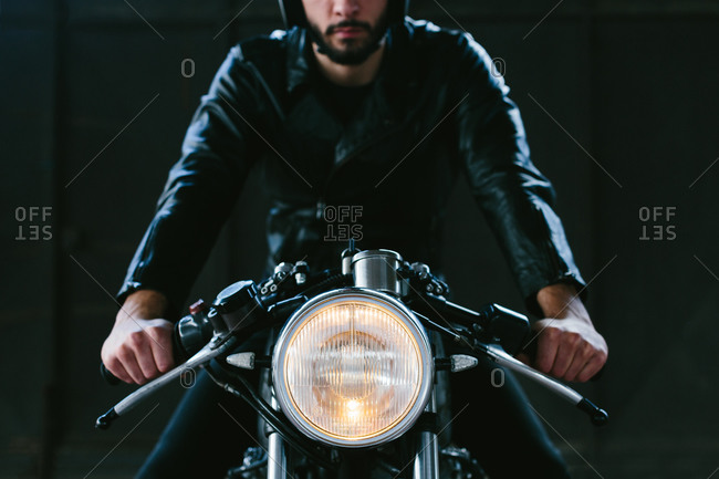 Young male motorcyclist straddling vintage motorcycle in garage, cropped front view
