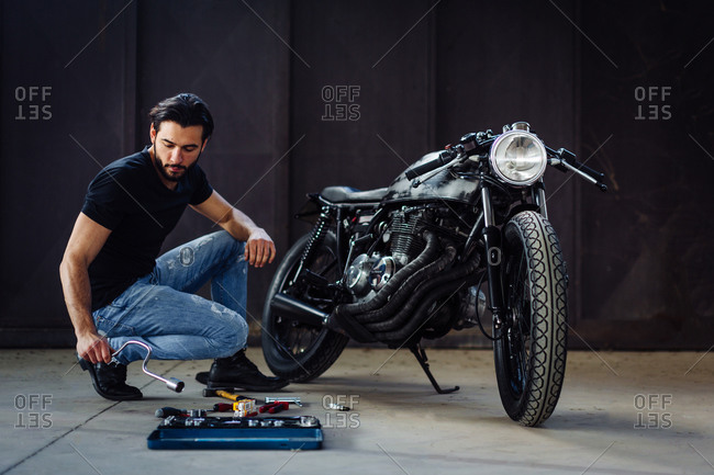 Young male motorcyclist doing maintenance on vintage motorcycle in garage