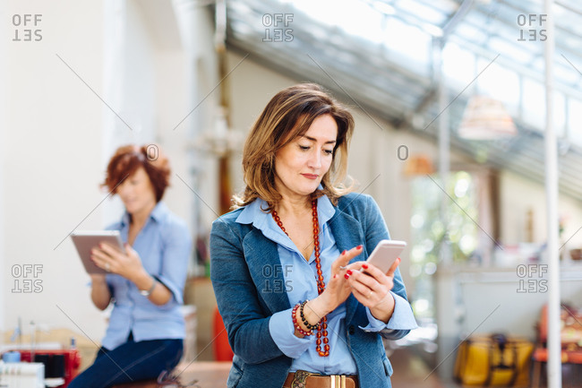 Two women, in creative studio, using digital tablet and smartphone