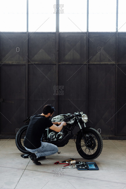 Young man kneeling to do maintenance on vintage motorcycle in empty warehouse