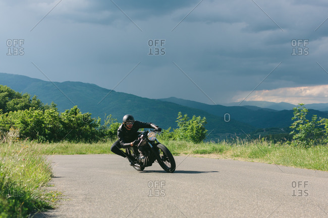 Young male motorcyclist on vintage motorcycle swerving around rural road bend, Florence, Tuscany, Italy