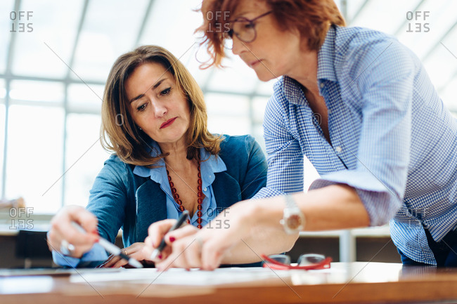 Two women, sitting at table, problem solving