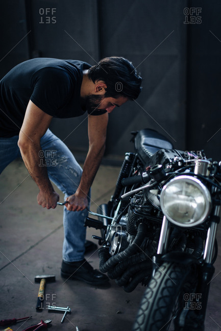 Young male motorcyclist repairing vintage motorcycle in garage
