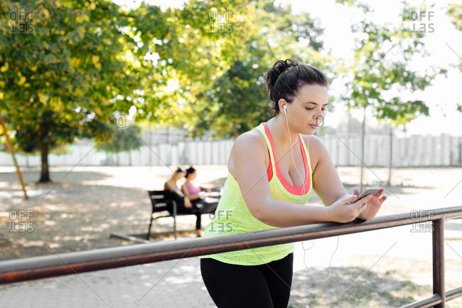 Woman using cellphone in park, friends taking break in background